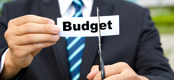 Event professional in a suit with scissors cutting a piece of paper with the word budget on it