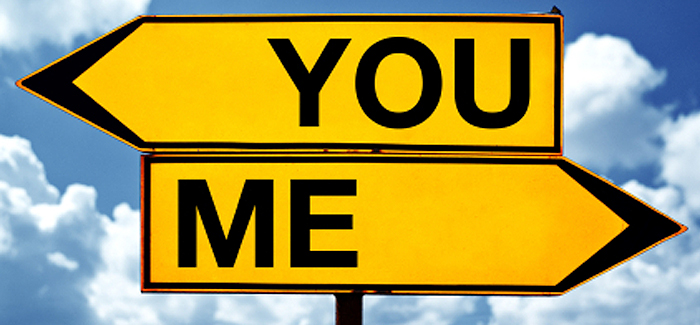 """Yellow arrow street signs pointing in opposite directions with one saying """"me"""" and the other """"you"""""""